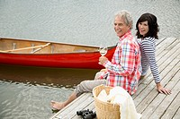 Mature couple enjoying some wine at the end of their boat dock (thumbnail)