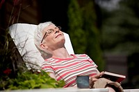 Middle_aged woman relaxing on lounger with book