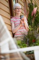 Middle_aged woman having a coffee outside her cottage