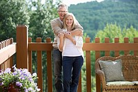 Portrait of middle_aged couple hugging on outdoor deck
