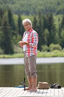 Senior man baiting fish hook while standing on dock