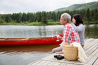 Mature couple starring off while sitting on boat dock (thumbnail)