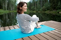 Pretty, middle_aged woman relaxing on yoga mat on boat dock