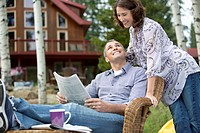 Couple reading the newspaper together outside cottage