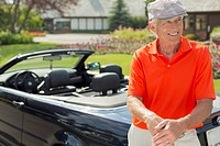 Senior golfer standing by sporty car