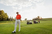 Senior man walking on fairway with golf clubs (thumbnail)