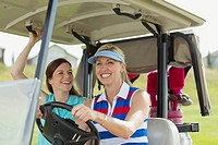 Two female golfers laughing in golf cart together
