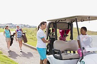 Foursome of female golfers with golf cart