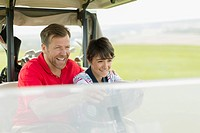 Father and son laughing and driving golf cart together