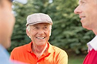 Senior golfer in discussion with fellow golfers