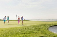 Foursome of female golfers walking off green