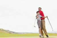 Father giving pre_teen son a bear hug on the golf course.