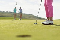 Close_up of golf ball and putter with female golfers in background.
