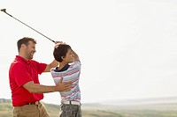 Father assisting son with golfing form and style