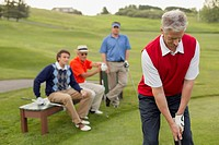Foursome of male golfers watching as one tees off