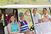 Portrait of four female golfers by golf cart
