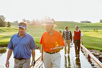 Foursome of male golfers walking across bridge on fairway