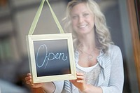 Woman behind glass door showing open sign (thumbnail)