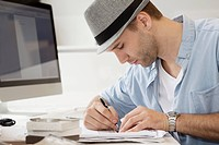 Profile of young man writing at desk (thumbnail)