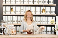 Portrait of female employee standing behind counter