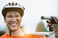 Young adult male mountain bike rider with mud on his face