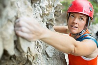 Middle-aged female rock climber on rock face (thumbnail)