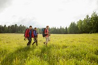 Three backpackers walking through meadow