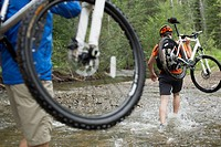View from behind of mountain bikers carrying bikes through stream