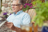 Middle_aged man reading newspaper outdoors