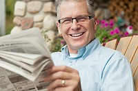 Portrait of handsome, middle_aged man reading paper outdoors.