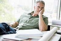 Middle-aged office worker looking bored at desk (thumbnail)