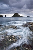 Waves swirl around the rocky seashore of Vagar, looking towards the beautiful island of Tindholmur in the Faroe Islands, Denmark, Europe