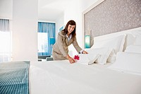 Chambermaid cleaning bed