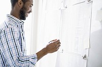 African American businessman reviewing plans on whiteboard