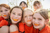 Soccer girls making faces with oranges (thumbnail)