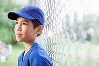 Young male baseball player standing by fence (thumbnail)