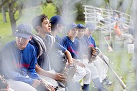Boys baseball team talking while sitting on bench