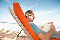 Man reading book on sunlounger