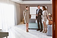 Hotel worker and couple in hotel room