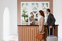 Female receptionist in hotel reception giving keys to guests