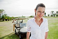 Portrait of smiling woman on golf course with man standing near golf cart in background