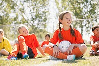 Girls soccer team sitting on grass together (thumbnail)
