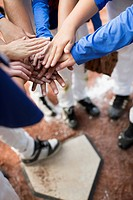 View from above of baseball players hands over hands at homeplate (thumbnail)