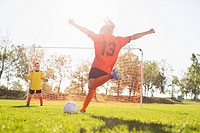 Young female soccer player about to kick soccer ball