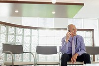 Doctor on a phone call while sitting in waiting room