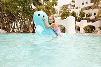 Girl 8-9 on inflatable toy in swimming pool (thumbnail)