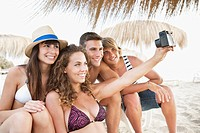 Happy friends on beach taking photo