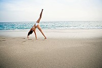 Woman doing handstand on beach