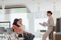 Pregnant couple talking with doctor in waiting room