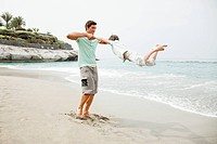 Father swinging son 6_7 on beach